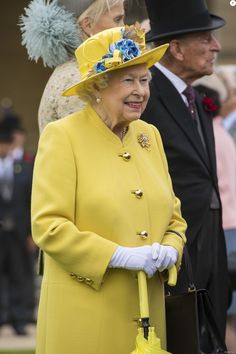 Britain's Queen Elizabeth II gestures as she walks, after observing a minute's silence at the start of a Special Garden Party, at Buckingham Palace in London on May 23, 2017.