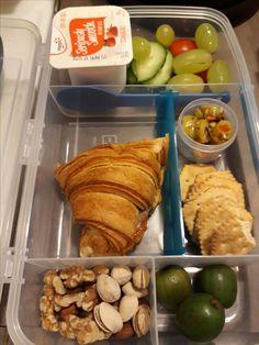 Ham and cheese croissant, yogurt, fruits, veggies, crackers and stuffed olives.