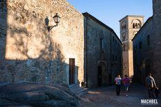 Dos jóvenes suben una calle en cuesta con la torre de la iglesia al fondo. Trujillo, Extremadura
