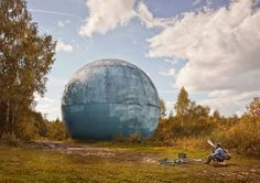 Picture of giant ball in forest with man sitting in front of it