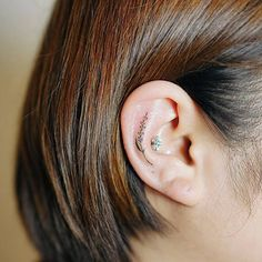 Small Lavender Tattoo on Ear by Nando Tattoo