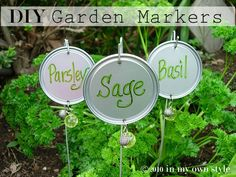 Plant markers made with coat hangers and can lids. The beads keep birds and other critters away