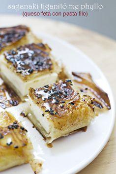 Saganaki, receta griega con queso feta, con miel, limón, mastija y sémsamo; envuelto en pasta filo y frito con aceite de oliva.