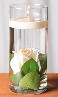 I will be doing this with 7 1/2 inch tall glasses from the Dollar Tree store as a part of the reception table centerpieces, which is as tall as a wine glass. The rose at the bottom would be orange with the candle being white. Mom and I will be putting navy blue ribbons around them and hold them together with a silver-colored wax seal somewhere between the candle and the rose. (Just like the ones on our wedding invitations.)