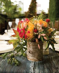 Gloriosa lilies, passion vine, maple leaves, fresh herbs, and dahlias in bark-wrapped vases, along with mushrooms, local foliage, and other forest accents, have a bucolic look.