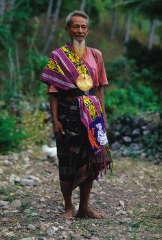 Paolo da Costa, one of the three cousins in charge of Ili Kere Kere Cave, shows off his traditional East Timorese clothing. A brilliantly colored cloth, woven in striking geometric patterns, is worn wrapped around the body. Large metal medallions are also worn on special occasions..Since the Indonesians left East Timor in 1999, the family has again begun caring for the ancient site.