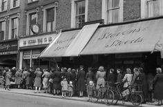WWII Shopping and Food, England-Shoppers wait patiently in a queue. This photo was taken in London in 1945. There had been rationing in Britain since 1940.