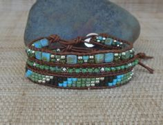 Single leather wrap bracelets crafted in shades of turquoise, olive and silver. May be worn individually for a minimal look, or stacked/layered to create your own unique style.  Bracelet #1. Single turquoise Picasso beads with silver nugget accents - 1/4 wide. Bracelet #2. Seed beads in a diagonal pattern - 3/8 wide. Bracelet #3. Square tila and seed bead mosaic pattern - 3/8 wide  All the beads are hand woven onto natural light brown leather cord using matching thread, and each bracelet has…
