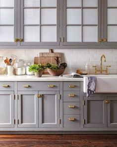 Grey kitchen cabinetry and white backsplash tiles