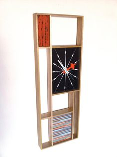Jetsetretrodesign - t h e f u t u r e w a s n o w  We are pleased to offer this beautiful Modernist Clock inspired by early designs of the 50s and 60s.  This clock is a high quality reproduction of the sunbeam Modrian clock from the early 1960s with a few key differences -  Large Version 3 x 12 Produced from top quality solid golden maple hardwood instead of the thin, plastic of the original models that often discolours or cracks. Orange fabric panel, black and multicolour faces are…