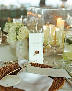 The ocean theme is carried through to the tablescape, with the napkins and table numbers both decorated with shells, at Megan and Clayton's Sea Island, Georgia wedding. White flowers are placed in vases that even have a touch of beach style.