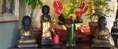 Stone Buddha's in Buddhist meditation postures decorated with beautiful flower vase and pots. Background sari curtains and pillow covers. Buddhist Meditation Techniques, Brass Statues, Gods And Goddesses, Flower Vases, Beautiful Flowers, Pillow Covers, Buddha, Hand Painted, Indian