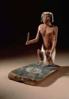 Ancient Egyptian wooden model of a woman tending a fire,gessoed and painted.  Artist unknown; ca. 2134-1991 BCE (First Intermediate Period or early Middle Kingdom).Now in the Los Angeles County Museum of Art.