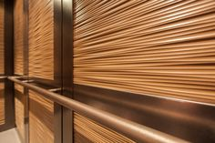 CabForms Series 2000-N Elevator Interior with inset panels in Bonded Gold Bronze with Natural Patina and Mara pattern; stiles and rails in Fused Bronze with Sandstone finish; Round handrails in Stippled Bronze at Newton-Wellesley Hospital, Newton, Massachusetts