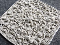 Rebirth is a crochet square featuring a central floral and starburst pattern…