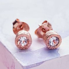A stunningly simple and elegant pair of stud earrings featuring a single semi precious white topaz stone in a naturally textured rose gold setting.