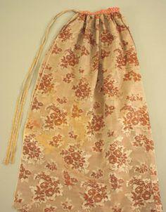 Förkläde. Silke, grått med blommor i brunt och silver-grått; röd linning med blommönster i vitt och blått, småblommigt; randigt knytband av bomull i rött, vitt, blått och gult.