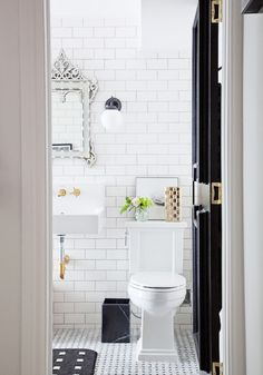 All white bathroom with white tiled walls, marble flooring, and a crystal mirror.