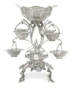 A George III sterling silver floriform nine-basket epergne by Thomas Pitts, London, 1768 - The central reticulated oval basket decorated with floral sprays and foliage above an openwork stem issuing two tears of foliate-sheathed scrolling arms suspending further swing-handle baskets, joined by fruiting branches on downswept legs ending in leafy bud feet; total weight approximately 156oz troy height 21in (53.25cm); diameter 18in (45.75cm).