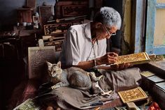 Photo by @stevemccurryofficial // The woodcarver's cat and her kitten keeps him company as he carves a prayer book, a craft for which there is no room for error. From this block alone, hundreds of copies will be made that will be used for teaching and individual worship. As the influx of new technologies makes it cheaper and easier to reproduce these works mechanically, such crafts are quickly becoming extinct. Image taken in Dharamsala, Himchal Pradesh, India