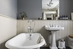A bathroom sports a freestanding tub, a pedestal sink, and a wall sconce from Bestlite.