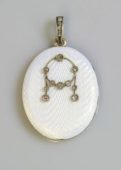 A Fabergé gold and silver diamond set locket, St. Petersburg 1908-1926. The oval hinged locket with white guilloché enamel to an engine turned, draped ground. An applied rose cut diamond set wreath or festoon and garlands, with a rose cut diamond set bale. Workmaster mark possibly that of Feodor Alexeievich Afanasiev.