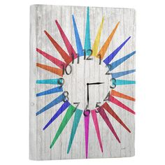 Reclaimed wood wall clock with a multicolor starburst motif.