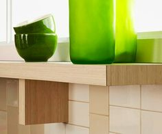 Sweet Shelf  Laminate a shelf in the same way the kitchen island was laminated to create a cohesive look for the kitchen surfaces. Keep in mind when cutting hollow-core doors, be sure to cap any open ends with a piece of wood lath cut to size and stained to match the laminate. Arrange bright green vases and cups on the shelf to add a burst of color to the otherwise plain surface.