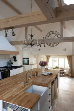 Multi-level open plan kitchen with neutral colours and belfast sink.