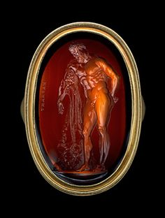 Hercules Intaglio ring. Gold ring, the oval bezel enclosing a sard intaglio figure of the Farnese Hercules, bearded, leaning with his left arm on his club which rests on a rock covered by the lion's skin. He stands three quarters to the front, his head in profile. Signed in Greek letters MARXANT (Nathaniel Marchant, 1739-1816), 1780-1784. Formerly Esmerian Collection.