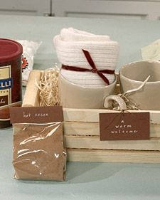 "Cute Gift - Hot Chocolate, Mugs, Wooden Basket and a tag reading ""A Warm Welcome""."