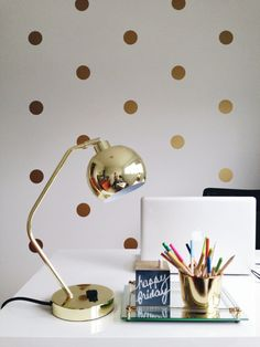 Polka dot vinyl stickers on a off white wall in an office with a golden lamp and laptop.