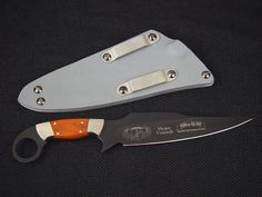 """Special Operations Forces Bulldog"""" by Jay Fisher.  It is a well thought out, serious combat knife. The knife is made to be pulled out of the sheath with the free hand, immediately and quickly by the finger ring, which is secured by the index finger. The long, sharp, stout blade is instantly in the combat defensive position, and any enemy behind or beside is vulnerable to its spear point razor keen edge, and with seven inches of blade length, the point has lethal reach."""