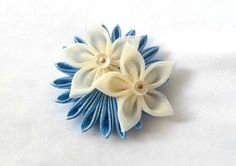 This is a 2.5 inch Kanzashi flower hand folded out of blue metallic lame and cream organza. The centers are vintage shoe buttons, and it fastens in the hair with a small alligator clip.  DISCLAIMER: Scarlett and Maria accessories are designed for adult use ONLY. Scarlett and Maria accessories should NEVER be worn by any person 12 years old or younger. The buttons and other small embellishments are CHOKING HAZARDS  IMPORTANT NOTE: If you are trying to match a specific color, please be mindful…