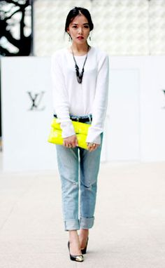 slightly oversized white crew neck long sleeve shirt; thick, relaxed gunmetal chain necklace; neatly cuffed boyfriend jeans; center parted low bun; large neon yellow clutch; delicate droplet earrings; pinky lips