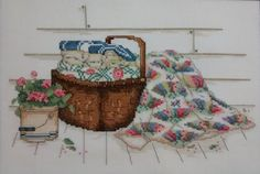 Completed Paula Vaughan cross stitch of flowers in a bucket with a basket of quilts.  Ready-to-frame. Stitched area is 7 x 11 on a piece of 12 x 18 14-count white Aida cloth.