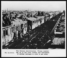 German demobilisation, Western Front, 1918. Scenes as German soldiers cling on to the roofs and doors of a train already full of other troops. The caption indicates that these were demobilised German troops desperately trying to return home. The photograph may have been taken in France.