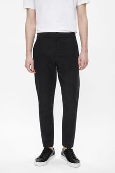Dropped at the crotch, these trousers are made from a comfortable cotton-mix with an elastic waistband. Tapered at the ankle, they have in-seam side pockets, back welt pockets and a hook zip fly.