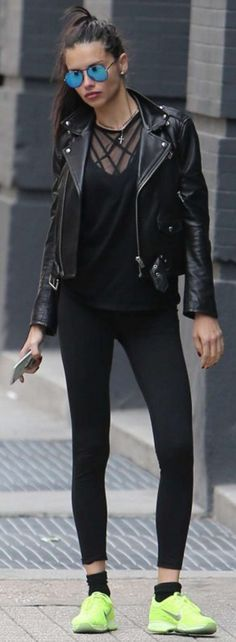 Who made Adriana Lima's black leather jacket, blue aviator sunglasses, and neon green sneakers?