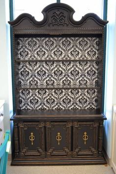 """Funky yet Elegant Painted Black China Cabinet with Damask Patterned Black and White Wall Papered Back - Has 2 glass shelves and 2 lower side cupboards - It even lights up!! - 49""""W x 16""""D x 82.5""""High - what a gorgeous addition to a kitchen or dining room."""