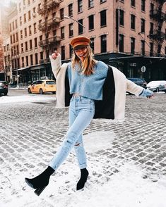 Cozy shearling jacket over blue sweater and denim jeans with cute cap.