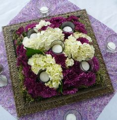 Low-profile wedding centerpiece made with a vintage frame, votive candles, fabric & flowers.