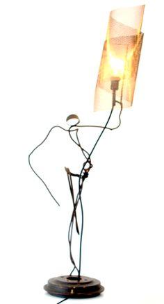 Portador de Tocha  Descrição: luminária de mesa que captura o movimento cotidiano na figura de um homem com uma tocha na mão. Quanto mais pontual a fonte de luz, maior é efeito de sombras e a movimentação, conforme o ângulo de observação.   Técnica: cúpula de tela de chapa perfurada em forma de espiral, base de tambor de freio de carro, arame de sucata e pintura com verniz fosco.  Peso: 6 kg Dimensão: 50x 100 cm
