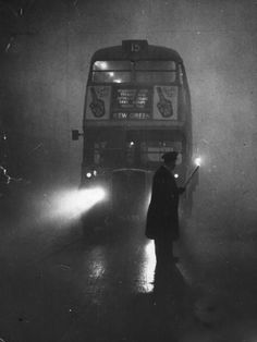 London Smog Disaster of 1952 ~ Looks like the chap leading the bus is carrying a lighted torch ~