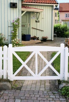 <strong>5. Trägrind – Öppen & luftig</strong><br>Grinden kan ha flera funktioner. Den kan stänga eller öppna. Denna enkla vita trägrind med sina två kryss ger ett öppet och luftigt intryck. Det passar bra till staketet som omger huset, som är lågt och lätt att se över. En lätt bågformad linje gör överstycket på ramen lite mer arbetad. Detta är en grind där katten smidigt tar sig igenom.