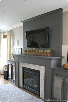 Love how the crown molding is painted the same deep gray to match the planked fireplace.