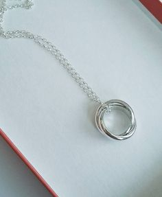 Sterling Silver interlinking ring pendant. It has a secret happy birthday message hand -stamped on the inside!