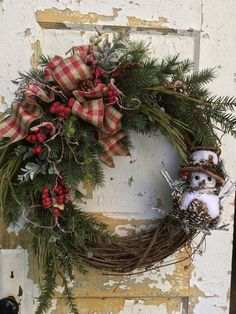 Rustic Christmas Wreath, Snowman Wreath, Holiday Wreath, Christmas Decor  This rustic Christmas wreath is filled with warmth and Christmas cheer. It is filled with beautiful evergreen boughs, grass curly stems, pine cones, berries, a plaid bow and finished with a beautiful snowman.  The finished size from tip to tip is 24 x 23 x 10.  Thank you for visiting my shop!  To view all my items visit: https://www.etsy.com/shop/FlowerPowerOhio?ref=hdr_shop_menu