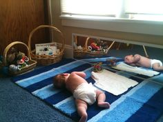 Montessori movement area for an infant which includes a mirror, a small selection of manipulative toys or materials and a soft mat to designate the space.
