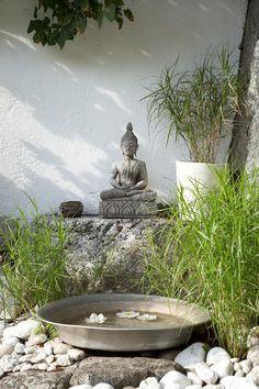 Buddha-Figur im Garten mit Natursteinen